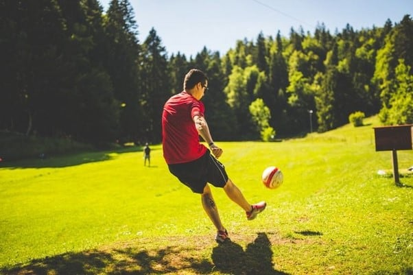 A Man Kicks A Football To His Friend On The Other Side Of The Field.