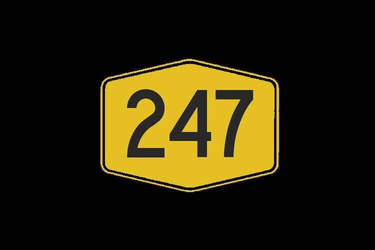 A yellow sign with the numbers 247 written in black on a black background