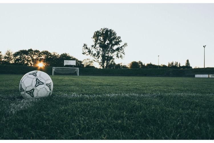 A Football lay at the Vicinity of a Lush Green Football Field, With the Sun Peering around the Corner