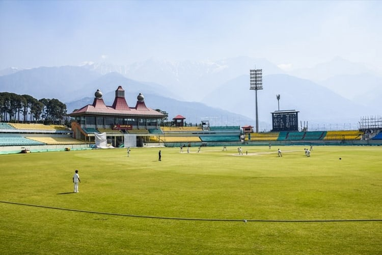 A game of cricket is taking place in a beautiful setting