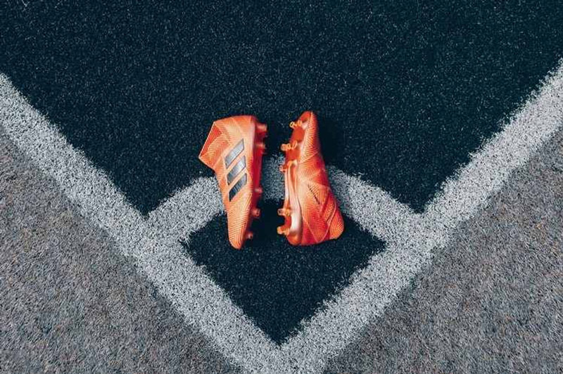 A Pair of Football Cleats Lay at the Corner Spot of a Football Field