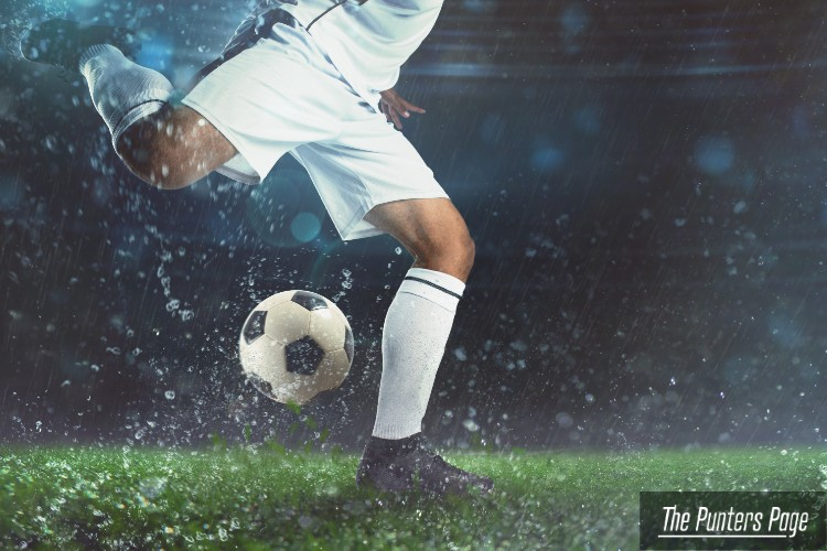Image of a player about to shoot a football ball in a stadium during night time while raining