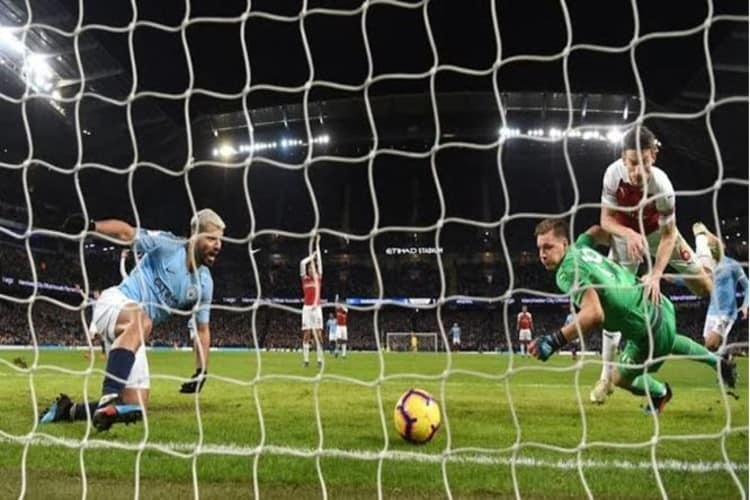 Sergio Aguero Scores a Goal Past Bernd Leno in a Match Contested Between Manchester City and Arsenal.""