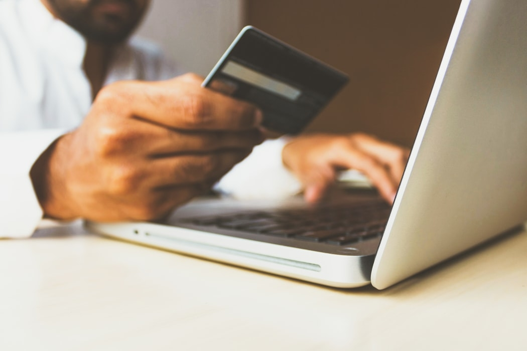 A person using his laptop holding a banking card