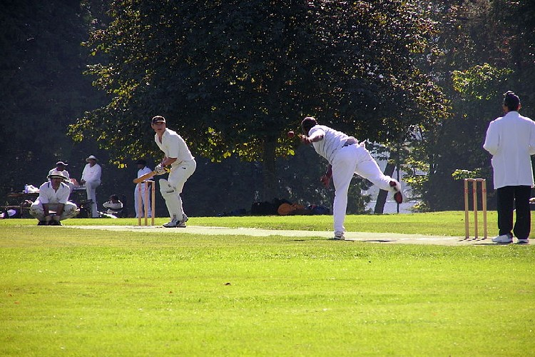 Players playing cricket at the park