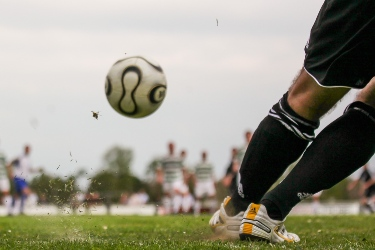 A shot of a football being kicked by a football player