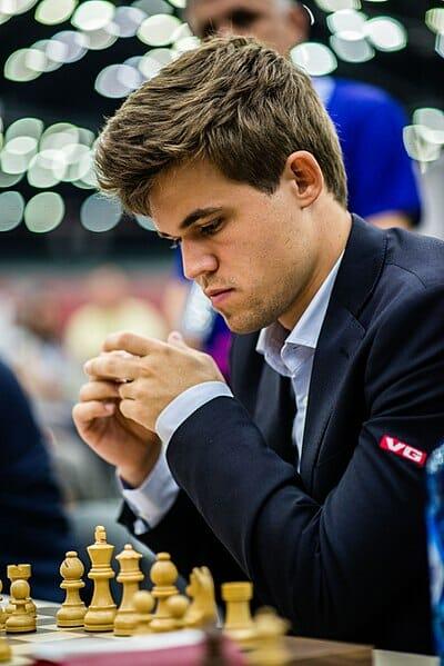 man looking at chess board