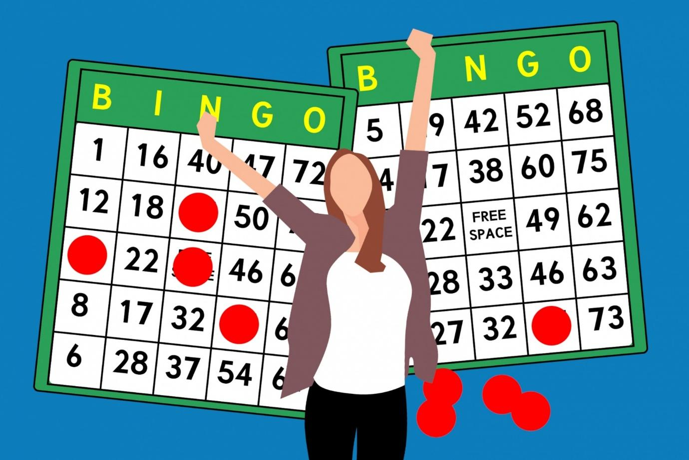 woman standing in front of bingo cards with arms raised