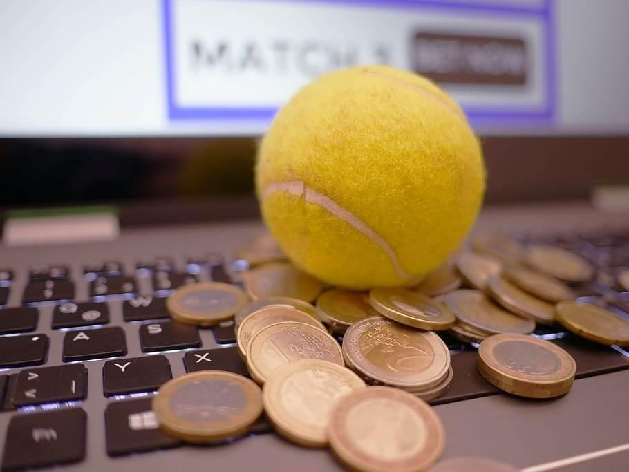 Tennis ball and coins on a laptop computer