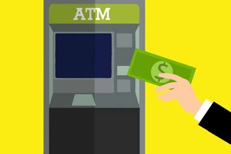 Image Of Man Putting Cash Into ATM