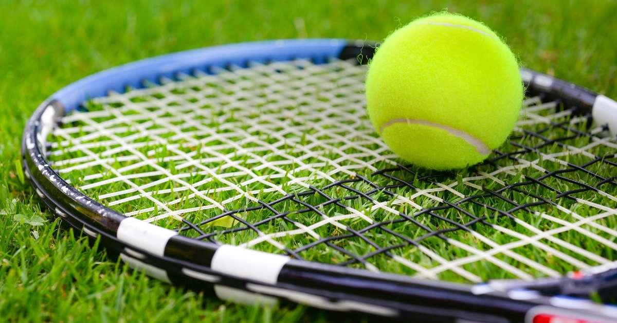 Tennis ball and racket on grass